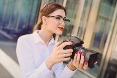 La belle jeune fille dans la chemise blanche se tenant dans des mains l'appareil-photo appuie sur le bouton de volet et regarde d photo stock