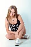 La belle jeune fille dans des shorts de jeans et des sports chaussent se reposer dans le studio sur le fond blanc-bleu photographie stock libre de droits