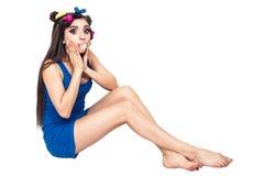 La belle jeune fille dans la robe bleue avec des bigoudis s'assied sur le plancher et m?che le ruminage photos libres de droits