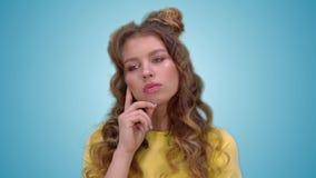 La belle jeune fille dans un T-shirt jaune réfléchi et considère Plan rapproché clips vidéos