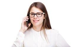 La belle jeune fille dans une chemise blanche sur le blanc a isolé le fond parlant à un téléphone portable Sourit le portrait au Photos libres de droits