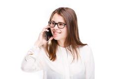 La belle jeune fille dans une chemise blanche sur le blanc a isolé le fond parlant à un téléphone portable Sourit le portrait à l Images stock
