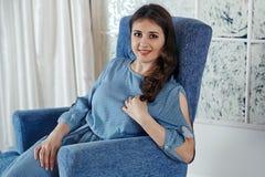 La belle jeune fille de brune dans une robe bleue s'assied sur un bl Image libre de droits