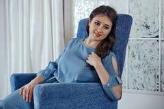 La belle jeune fille de brune dans une robe bleue s'assied sur un bl Photographie stock libre de droits