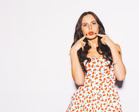 La belle jeune fille de brune posant dans une robe courte d'été et un baiser rouge de lèvres fait le doigt à ses lèvres Photos libres de droits