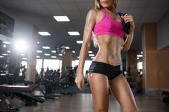La belle jeune fille de forme physique sexy exécutent l'exercice avec l'extenseur dans le gymnase photographie stock libre de droits