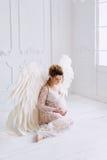 La belle jeune fille enceinte avec le grand ange s'envole Photographie stock