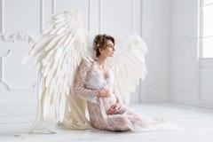 La belle jeune fille enceinte avec le grand ange s'envole Images libres de droits