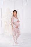 La belle jeune fille enceinte avec le grand ange s'envole Photos libres de droits