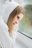 La belle jeune fille est triste à l'hublot photographie stock