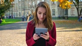 La belle jeune fille, l'étudiant passant en revue, transmission de messages sur le comprimé, obtient frustrée et alors amusée, en banque de vidéos