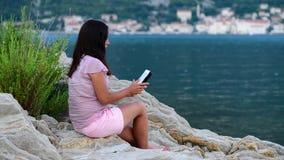 La belle jeune fille lit un comprimé et des rêves près de la mer banque de vidéos
