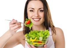 La belle jeune fille mange de la salade Photo stock