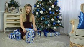 La belle jeune fille met des cadeaux sous un arbre de Noël Photographie stock