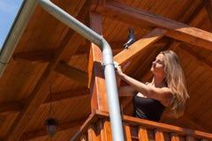 La belle jeune fille peint un belvédère en bois Travail d'été dans le jardin La belle brune enduit les faisceaux en bois Images libres de droits