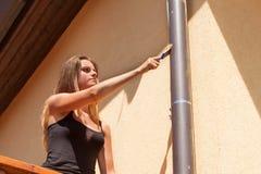 La belle jeune fille peint un belvédère en bois Travail d'été dans le jardin La belle brune enduit les faisceaux en bois Photographie stock libre de droits
