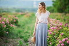 La belle jeune fille porte les vêtements sport ayant le repos dans un jardin avec les roses roses de fleur Photographie stock libre de droits