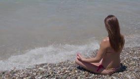 La belle jeune fille s'assied dans une pose de lotus sur la plage 4K clips vidéos