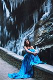 La belle jeune fille s'assied sur une haie en pierre sur un fond d'un massif et d'un glacier de montagne Photos stock