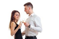 La belle jeune fille se tient à côté d'un jeune homme attirant et d'une Champagne potable Image stock