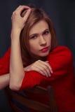 La belle jeune fille se tient sur un fond noir Photo stock