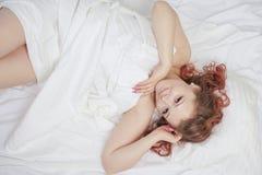 La belle jeune fille se trouve sur un lit blanc et apprécie le matin la femme caucasienne de charme est heureuse et détente somno photo stock
