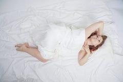 La belle jeune fille se trouve sur un lit blanc et apprécie le matin la femme caucasienne de charme est heureuse et détente somno image libre de droits