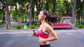 La belle jeune formation modèle de fille fonctionne en parc, mouvement lent clips vidéos