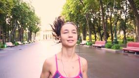 La belle jeune formation modèle de fille fonctionne en parc, mouvement lent banque de vidéos