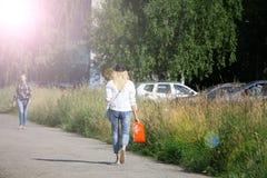 La belle jeune IRL bien habillée asiatique tenant un sac brun de papier blanc et fait des achats dans un magasin en ligne contre  photos stock