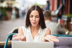 La belle belle jeune jolie femme souffle le baiser d'air dans l'écran de l'ordinateur portable, fait la vidéo calorie, a la conve photos libres de droits
