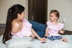 La belle jeune mère avec sa petite fille se trouve sur le lit Photo libre de droits