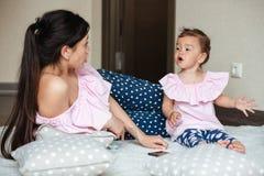 La belle jeune mère avec sa petite fille se trouve sur le lit Photographie stock libre de droits