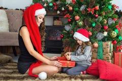 La belle jeune mère fait à la petite fille un cadeau de Noël Photo stock