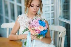 La belle jeune mariée a abaissé ses yeux à son bouquet des fleurs Une fille dans une robe blanche admire les roses image libre de droits