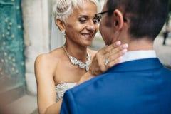 La belle jeune mariée avec de longues prises de boucles toilettent la main du ` s pendant une promenade photo stock