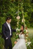 La belle jeune mariée avec le fiancé balance sur une oscillation photos libres de droits