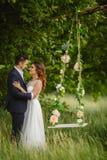 La belle jeune mariée avec le fiancé balance sur une oscillation image stock
