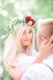 La belle jeune mariée brille tout en tenant la tête du ` s de marié dans des ses bras Photographie stock