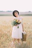 La belle jeune mariée dans la robe et le chapeau noir de mariage de vintage tient le bouquet coloré et la vieille valise au Photographie stock