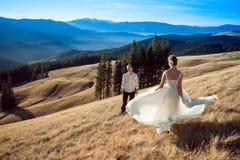 La belle jeune mariée danse avant que son marié sur le champ Lune de miel dans les Alpes Images libres de droits