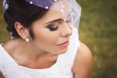 La belle jeune mariée disposant à obtenir s'est mariée dans la robe et le voile blancs Photographie stock libre de droits