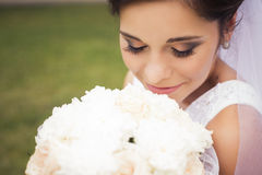 La belle jeune mariée disposant à obtenir s'est mariée dans la robe et le voile blancs Photographie stock