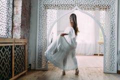 La belle jeune mariée tourne autour elle-même dans la danse La brune gaie pose dans la robe de flottement dans un vintage Image stock