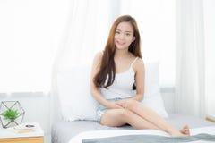La belle jeune séance asiatique de femme de portrait et sourient la fenêtre à la chambre à coucher tandis que réveillez-vous avec photographie stock