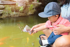 La belle mère asiatique est salut vos poissons de alimentation de bébé mignon Images stock