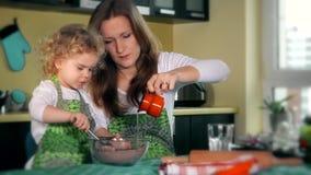 La belle mère enseigne la fille préparent la pâte dans la cuisine Famille heureux clips vidéos