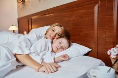 La belle mère et la fille embrassent et se situent dans un lit Photos stock