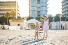 La belle mère heureuse s'attaque main dans la main avec le fils mignon de sourire à la plage Image libre de droits