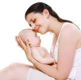 La belle mère heureuse se tenant dessus remet son bébé de sommeil mignon Photo stock